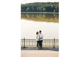年轻的高加索男子拥抱怀孕的妻子_6435127
