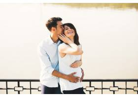 年轻的高加索男子拥抱怀孕的妻子_6435485