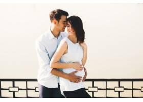 年轻的高加索男子拥抱怀孕的妻子_6435491