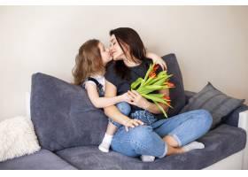 可爱的小女孩拥抱她漂亮的母亲_7146664