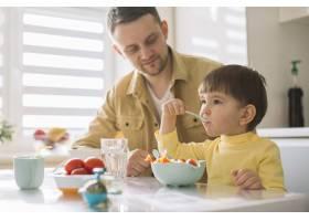 可爱的小孩子和他的父亲在吃麦片_7500397