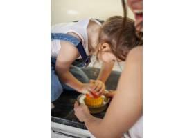 可爱的年轻女孩和准备橙汁的母亲_7146719