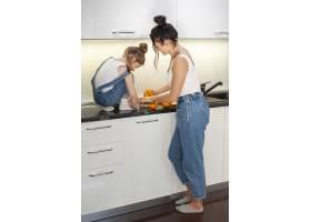 可爱的年轻女孩和正在准备橙汁的漂亮妈妈_7146703