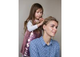 可爱的年轻女孩玩弄妈妈的头发_7146624