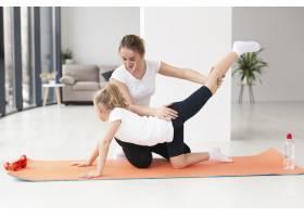 女儿在家和母亲一起锻炼的侧观_7435888