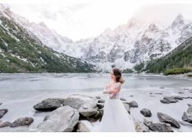 冬天冰冷微笑的女孩穿着婚纱站在结冰的高_7497145
