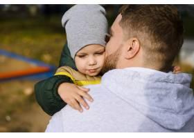 一个年轻人怀里抱着一个男孩_5761544