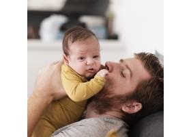 特写父亲亲吻身着黄色衣服的婴儿_6072467
