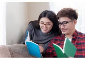 相爱的年轻夫妇坐在沙发上看书_5392748