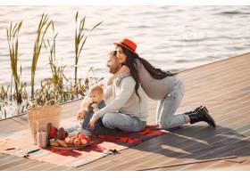 秋天公园里一家人带着年幼的女儿坐在水边_6212149