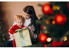 母亲带着女儿坐在圣诞树旁_6190726