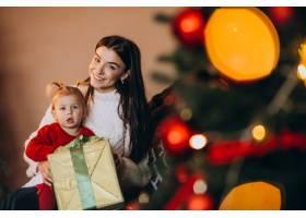 母亲带着女儿坐在圣诞树旁_6190846