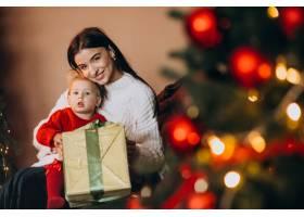 母亲带着女儿坐在圣诞树旁_6190847