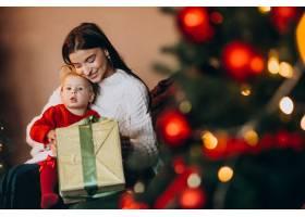 母亲带着女儿坐在圣诞树旁_6190848