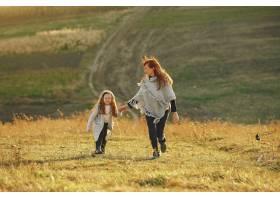 母亲带着小女儿在秋天的田野里玩耍_6280680