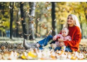 母亲带着小女儿坐在公园的秋叶上_6255250