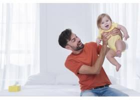 快乐的父亲在床上抱着孩子_6071171