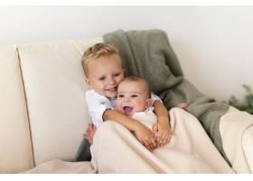 快乐的蹒跚学步的孩子拥抱可爱的兄弟姐妹_6145820