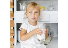 有趣的小女孩拿着一杯牛奶_5918640