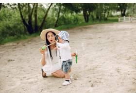 母亲和儿子在夏季公园里玩耍_5251274