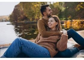 年轻夫妇坐在河边的甲板桥上_6190684