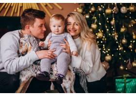 年轻的家庭带着女婴坐在圣诞树旁_6426678