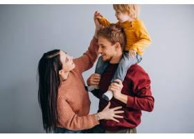 年轻的家庭带着年幼的儿子一起在灰色上_6426594