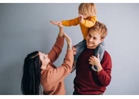 年轻的家庭带着年幼的儿子一起在灰色上_6426595