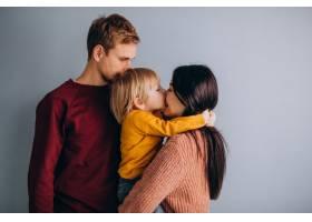 年轻的家庭带着年幼的儿子一起在灰色上_6426598