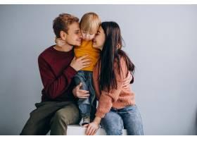 年轻的家庭带着年幼的儿子一起在灰色上_6426599