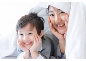 年轻的母亲和小男孩幸福地盖着毯子_5392799