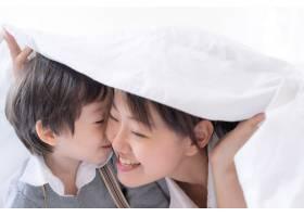 年轻的母亲和小男孩幸福地盖着毯子_5392800