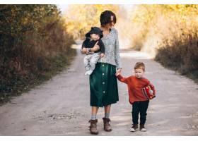 年轻的母亲带着两个儿子在公园散步_5852281
