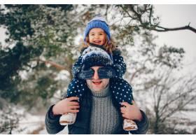 小女孩和父亲在冬季公园里玩耍_5913047