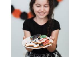 小女孩拿着一个装有饼干的盘子_5481441