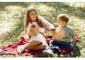 可爱的小孩子们坐在公园里吃着面包_6238749