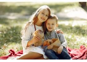 可爱的小孩子们坐在公园里吃着面包_6238751