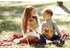 可爱的小孩子们坐在公园里吃着面包_6238752