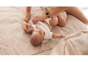 可爱的母亲给新生儿穿衣服_6008170