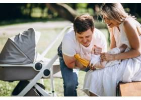 公园里的一对年轻夫妇带着他们的小女儿坐在_5495782