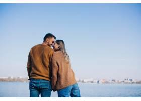 公园里站在河边的年轻夫妇_6190670