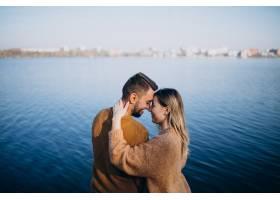 公园里站在河边的年轻夫妇_6190679