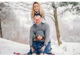 冬天公园里的一个小女孩父母坐在毯子上_5909796