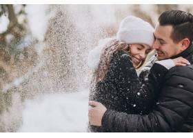 冬天的一对年轻夫妇在树上落下的雪下_6426728