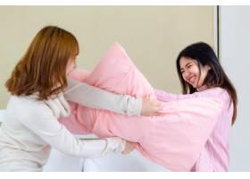 两名年轻女子玩格斗枕头_5433279