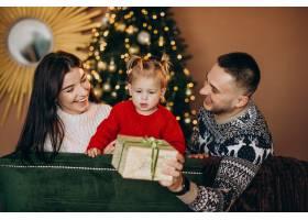 一家人带着小女儿坐在圣诞树旁打开礼品盒_6190867