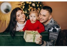一家人带着小女儿坐在圣诞树旁打开礼品盒_6190868