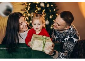 一家人带着小女儿坐在圣诞树旁打开礼品盒_6190869