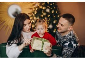 一家人带着小女儿坐在圣诞树旁打开礼品盒_6190870