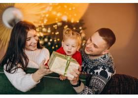 一家人带着小女儿坐在圣诞树旁打开礼品盒_6190871